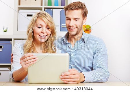 Happy young couple looking together on a tablet computer in the living room