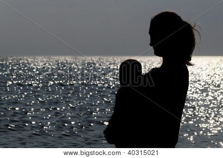 Mother And Child Silhouette On The Blue Sea