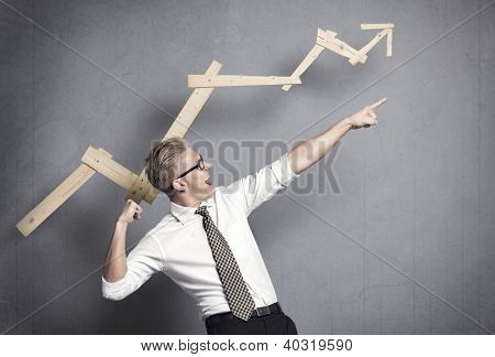 Concept: Successful business trend. Happy talented businessman pointing arm upwards in front of ascending business graph, isolated on grey background.