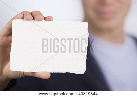 Closeup of white blank card with space for text in hand of a smiling blurred man in background.