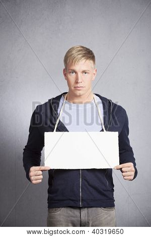 Serious man holding white blank signboard with space for text isolated on grey background.
