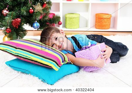 Little boy lying on pillows with gift in his hands under Christmas Tree waiting for Santa Claus to come