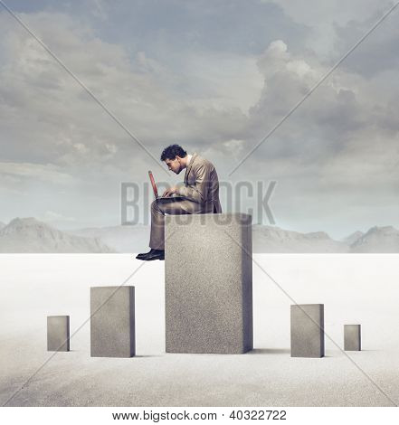Businessman using a laptop computer sitting on a concrete block in a desert