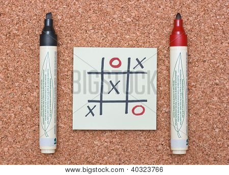 Tic Tac Toe Game With Red And Black Markers On Cork