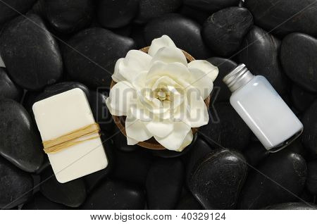 gardenia flower with wooden bowl with salt in glass, soap on black pebbles