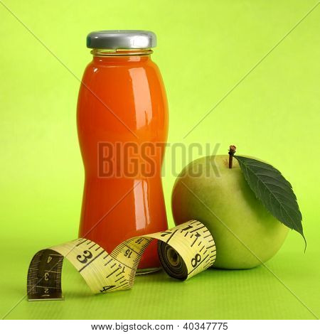 bottle of juice, apple and measuring tape, on green background