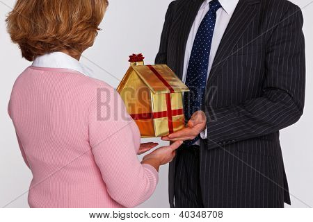 A businessman handing  a new home wrapped in gold paper with red ribbon and bow to a woman in casual clothing. Good concept photo for housing and property themes.