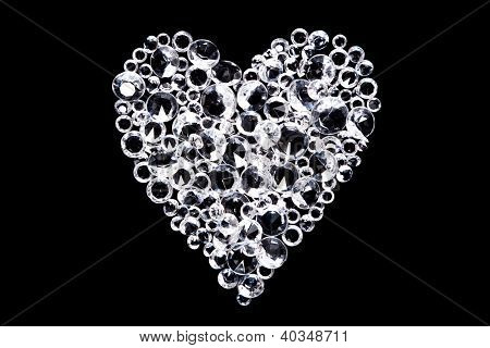 Imitation diamonds formed into a heart shape and isolated on a black background.
