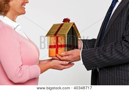 A businessman giving a woman a new home wrapped in gold paper with red ribbon and bow. Good image for house buying themes.