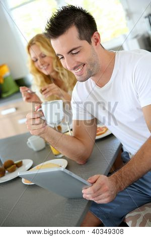 Young man sitting in home kitchen with tablet