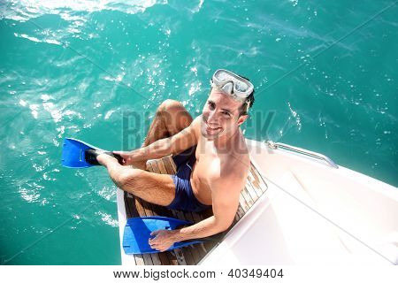 Young man on a boat steps putting flippers on