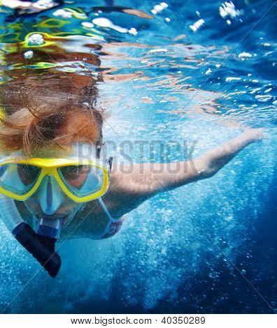 Close up underwater portrait of a woman in mask making bubbles in a sea