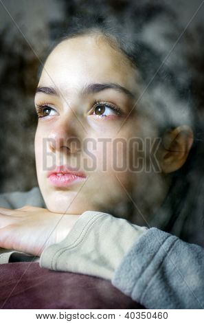 nostalgic girl looking through a window with winter trees reflected in the glass
