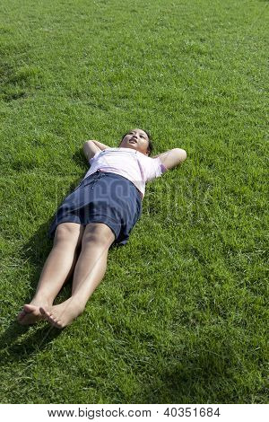 girl lied on green grass field wiht morning light