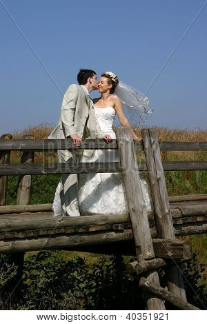 A just married couple kissing on a bridge