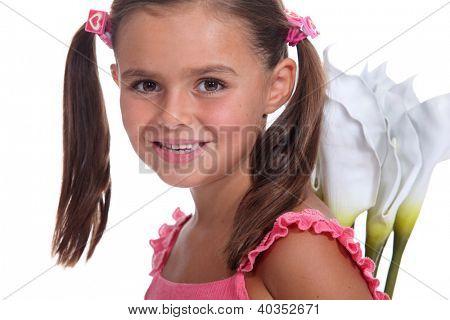 Little girl holding flowers behind back