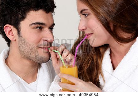 Couple sharing a glass of juice