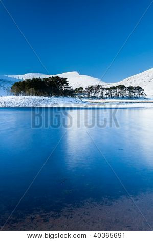 Snow Covered Mountains Reflected In A Semi Frozen Lake