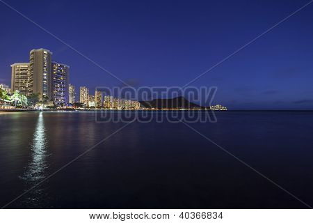 Waikiki Beach Honolulu Hawaii resort hotels and diamond head peak at night.
