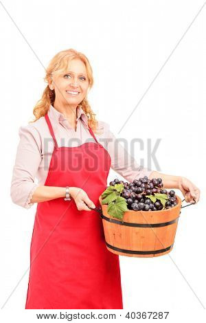 A female vintner holding a basket full of wine grapes isolated on white background