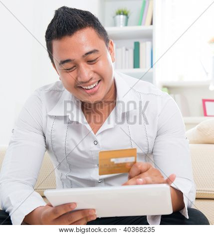 Southeast Asian man online shopping, hands holding credit card and computer tab sitting at home.
