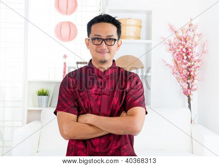 Chinese man in traditional Chinese Tang suit greeting standing indoors