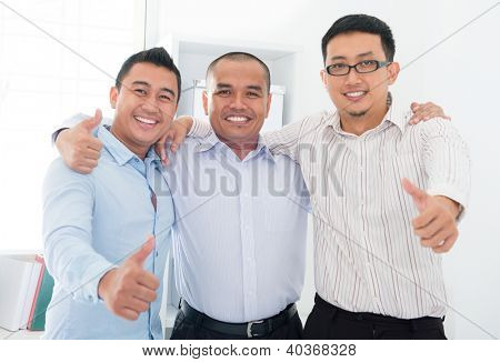 Thumbs up Southeast Asian businessmen standing in office