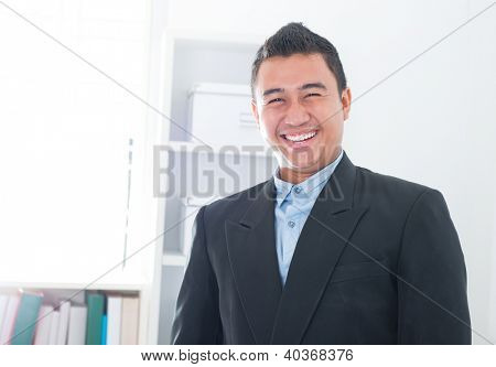 Attractive Southeast Asian executive standing in office