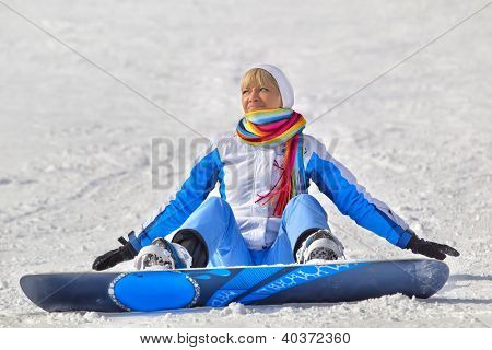 Young dissatisfied woman with snowboard sitting in the snow
