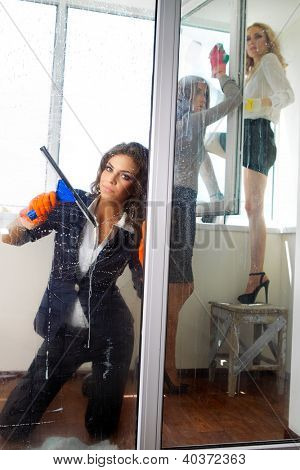 Young women cleaning her windows with squeegee cleaning