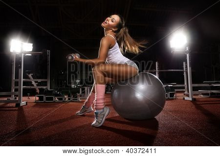 Woman Lifting Weights on Pilates ball workout posture in fitness club