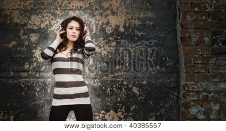 Young woman listening to music through headphones beside a grunge wall ideal for club graphics or event text