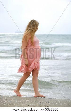 Portrait of beauty young woman in pink dress posing at a beach on sea background