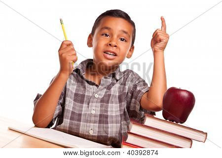 Adorable Hispanic Boy Raising His Hand Sitting with Books, Apple, Pencil and Paper Isolated on a White Background.