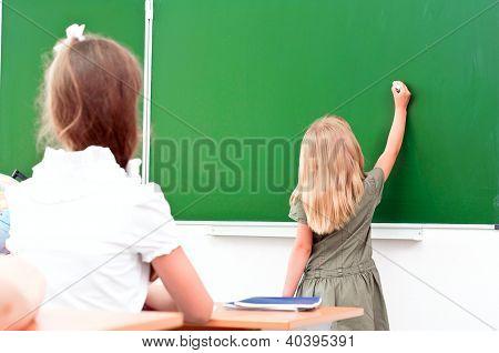 school girl writes on the blackboard