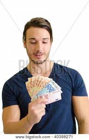 Successful Young Man Looking At Euro Banknotes