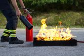 stock photo of infernos  - Instructor showing how to use a fire extinguisher on a training fire - JPG