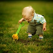 foto of shovel  - Cute little boy with a shovel looking for treasure - JPG