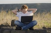 foto of underage  - Resting teen with mobile computer hold hands behind his head in nature at sunset - JPG