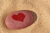 A red pebble on a beach with a wet heart shape upon it.