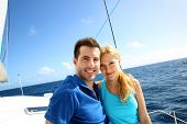 stock photo of sailing vessels  - Portrait of couple sitting on the top of sailing boat - JPG