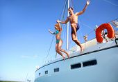stock photo of sailing vessel  - Young couple jumping in water from yacht - JPG
