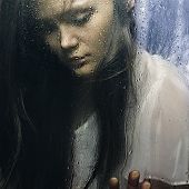 foto of boredom  - Art portrait of a beautiful young sadly girl standing at the window watching the rain - JPG