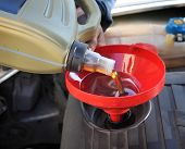 stock photo of lubricant  - Car servicing mechanic pouring fresh oil to engine - JPG