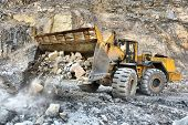 foto of wheel loader  - Wheel loader machine unloading rocks in the open - JPG