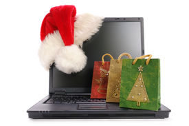 pic of santa claus hat  - Black open laptop with red santa claus hat put on lcd corner and christmas shopping bags  - JPG