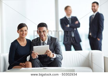 A young businessman and his colleague looking at camera while discussing data in notepad in working environment