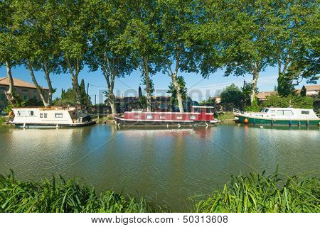CANAL DU MIDI, FRANCE - JUNE 22: Boats moored in summer on June 22, 2013 on the Canal du Midi, France. The UNESCO listed canal was built in 17th century stretching from Toulouse to Bezier.