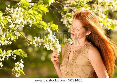 Mujer de pelo largo rojo permanente bajo la flor de cerezo