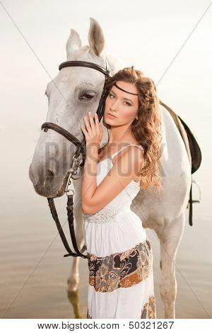 Beautiful woman on a horse. Horseback rider, woman riding horse on beach.